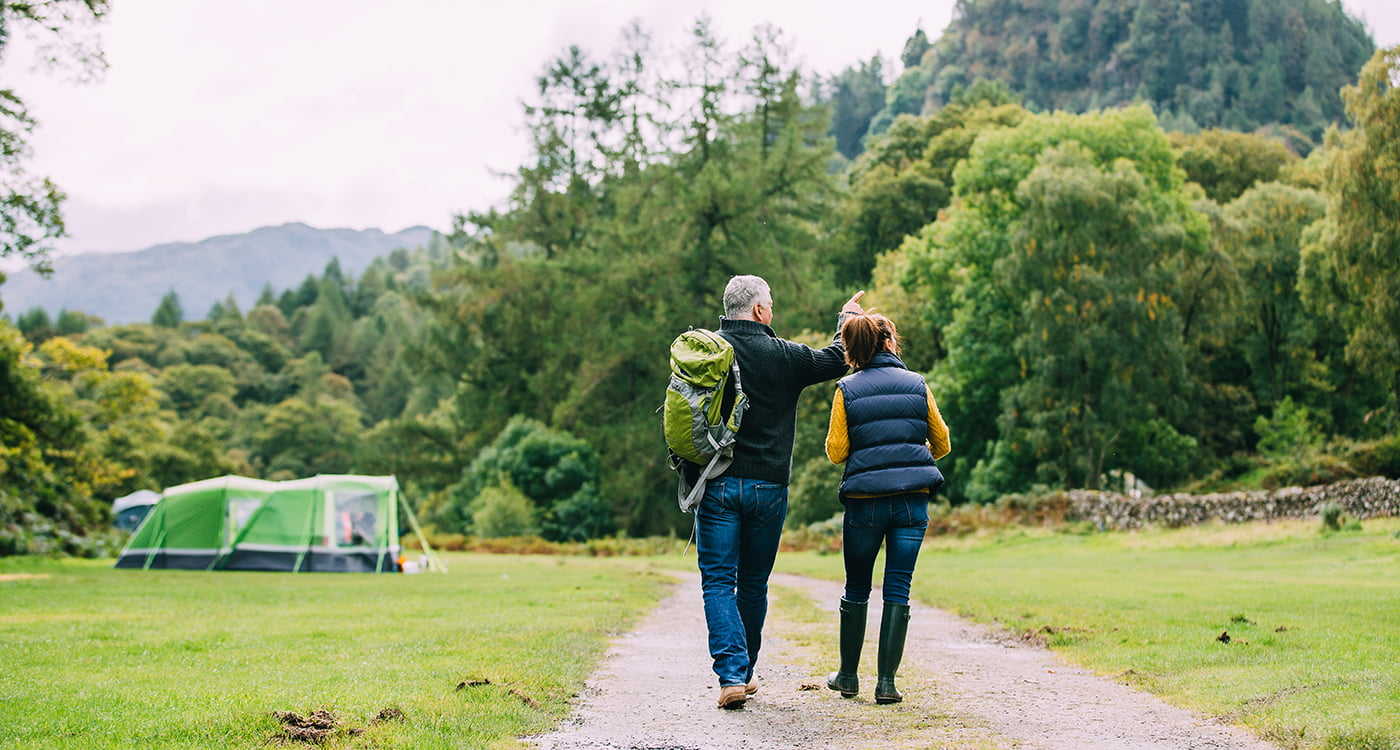 A man and a woman walking outdoors towards a campsite