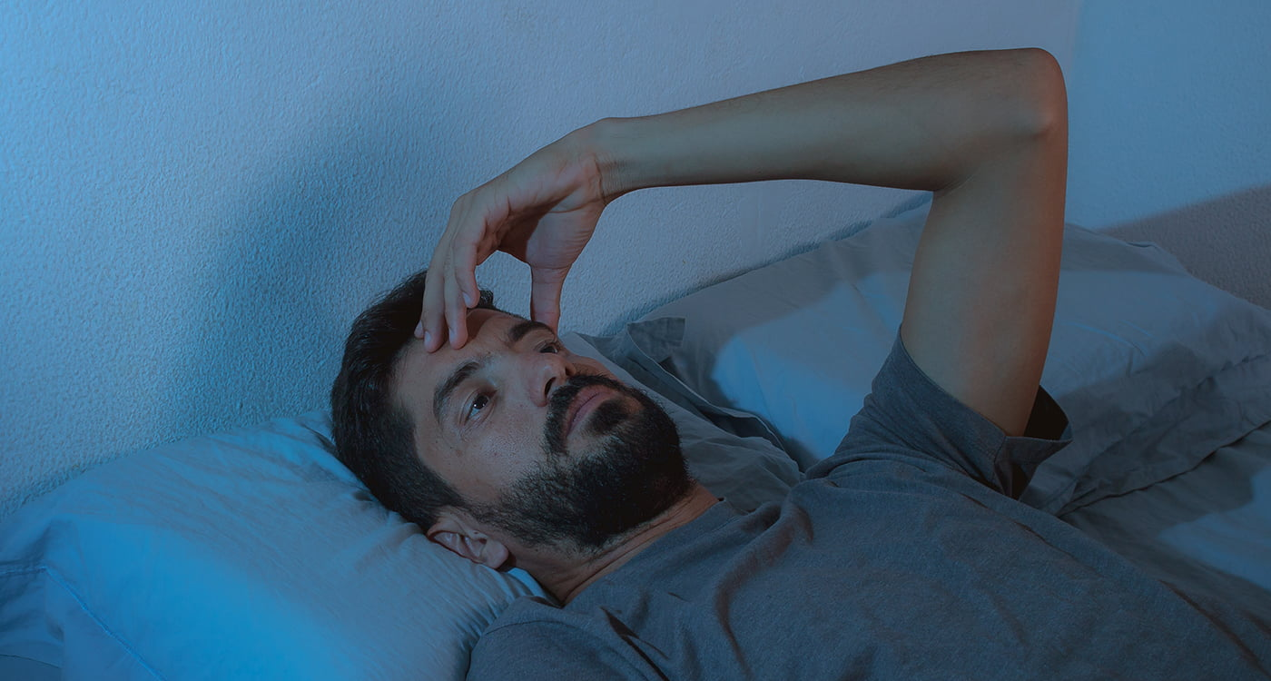 a man laying in bed with his hand on his forehead